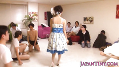 Oriental sexy girl in cute dress shows off to group of guys