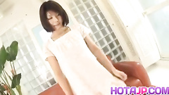 Cutie Japanese babe is pleasantly masturbating pussy on couch